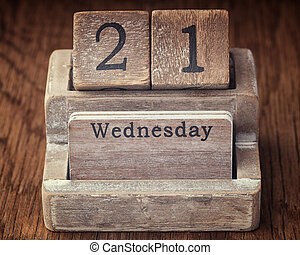Grunge calendar showing Wednesday the twenty first on wood background