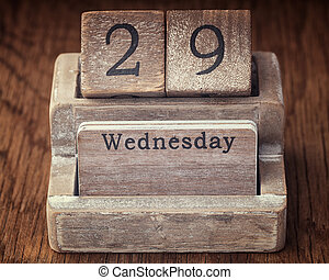 Grunge calendar showing Wednesday the twenty ninth on wood background