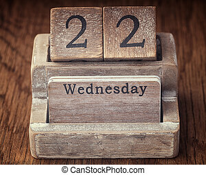 Grunge calendar showing Wednesday the twenty second on wood background