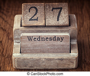 Grunge calendar showing Wednesday the twenty seventh on wood background