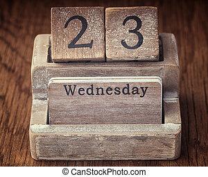 Grunge calendar showing Wednesday the twenty third on wood background