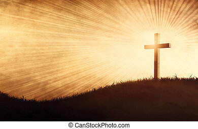 A cross on a grassy hill with sun beams.