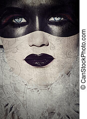 beautiful woman with gothic make-up covered in painted mask on grunge texture.
