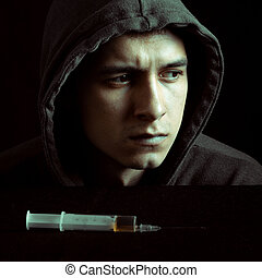 Grunge image of a depressed drug addict looking at a syringe and drugs