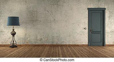 Grunge interior with blue door and floor lamp