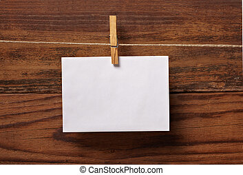 grunge note paper and clothes peg on wood - close up of a...