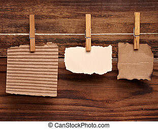 close up of a note paper and clothes peg on a wooden background