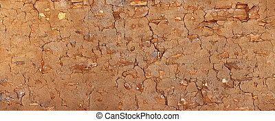 Grunge stone wall covered with clay plaster. Vintage architectural background