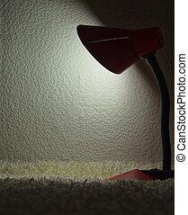 desk lamp shining on a dark wall