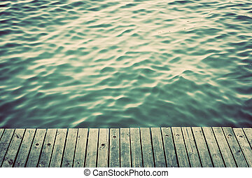 Grunge wood boards of a pier over ocean with rippling waves....