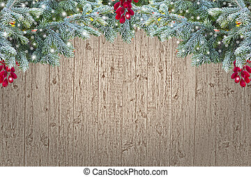 Vintage Christmas background - old grainy wooden planks decorated with blue spruce branches hoarfrost covered, red berries and snowflakes