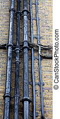 Black Pipes on Brick Wall