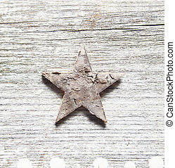 Grungy Christma background with a damaged peeling star centred on old textured cracked and weatherworn wood