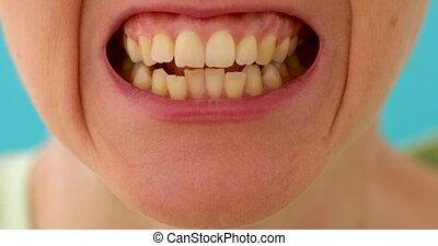 Grungy extreme closeup of human set teeth - Woman grins...