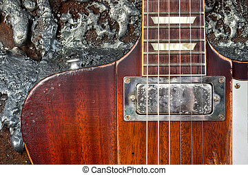 Closeup of vintage electric guitar with a grungy liquid metal backgroud