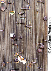 Battered old notice board with rusty tacks and staples on rough grain wood.