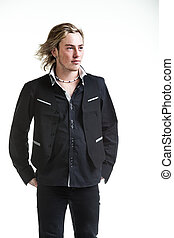 image of a grunge looking caucasian man wearing black and white formal attire with his hands behind his back and wind blowing through his hair