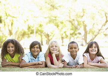grupa dzieci, leżący, na, żołądki, w parku