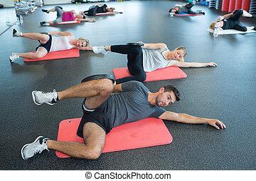 grupa ludzi, wykonując, nogi, w, sala gimnastyczna