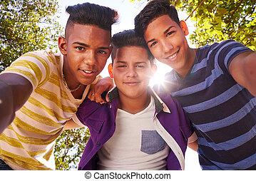 grupa, multiethnic, nastolatki, aparat fotograficzny, obejmowanie, uśmiechanie się