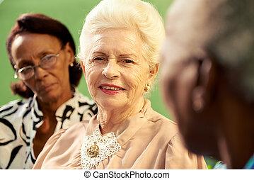 grupa, od, starszy, czarnoskóry i, kaukaski, mówiący kobietami, w parku