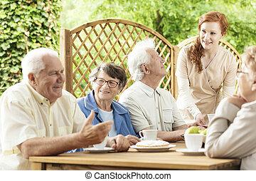 grupa, od, starszy, emeryci, cieszący się, ich, czas, razem, przez, niejaki, stół, zewnątrz, w, niejaki, ogród, od, niejaki, osamotnienie, home., młody, dozorca, assisting.