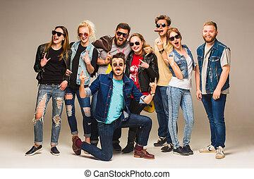 grupa, od, szczęśliwy, młody, przyjaciele, w, błękitne dżinsy, uśmiechanie się, na, przedimek określony przed rzeczownikami, aparat fotograficzny, przeciw, szary, tło.