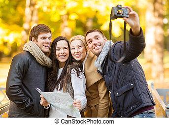 grupo amigos, com, câmera foto, em, outono, parque