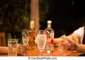 grupo amigos, desfrutando, bebendo, um, vidro champanhe, e, uísque, em, partido