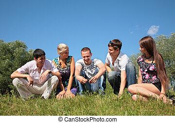 grupo, amigos, sentarse, en, pasto o césped, en, verano