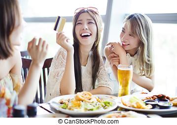 grupo, conversando, restaurante, mostrando, jovem, cartão crédito