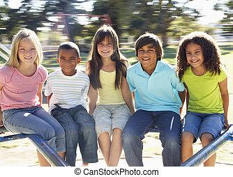 grupo crianças, montando, ligado, rotunda, em, pátio recreio