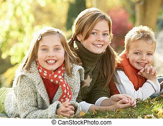 grupo, de, 3 crianças, realxing, ao ar livre, em, paisagem outono