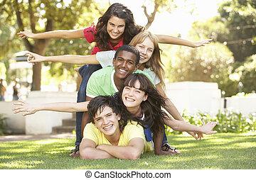 grupo de adolescentes, amontonado, en el estacionamiento