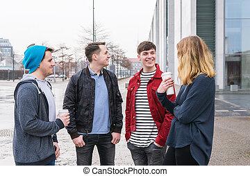 grupo, de, adulto joven, amigos, teniendo, un, conversación, mientras, posición, juntos, en, calle de la ciudad