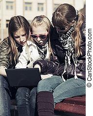 grupo, de, eduque chicas, con, computador portatil, sobre el banco
