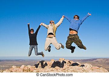 grupo, de, excursionistas, saltar, alegremente, en, cumbre de montaña
