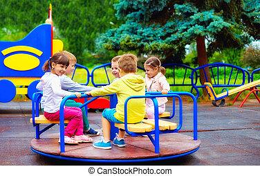 grupo, de, feliz, crianças, tendo divertimento, ligado, rotunda, em, pátio recreio
