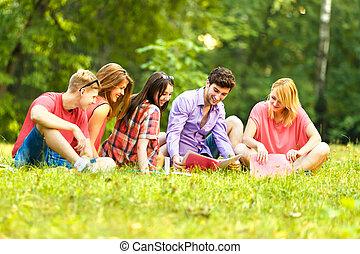 grupo, de, feliz, estudiantes, con, libros, en el parque, en, un, día soleado