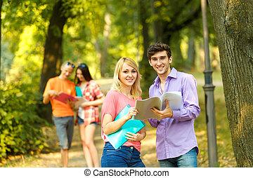 grupo, de, feliz, estudiantes, con, libros, en el parque, en, un, soleado, day.