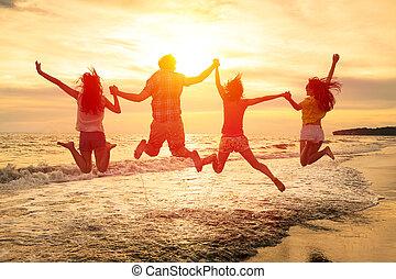 grupo, de, feliz, jóvenes, saltar, en la playa