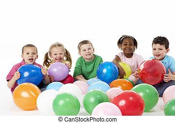 grupo, de, filhos jovens, em, estúdio, com, balões