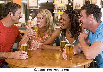 grupo, de, jovem, amigos, bebendo, e, rir, uma barra