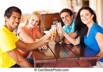 grupo, de, jovem, amigos, brindar, uma barra