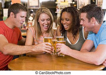 grupo, de, joven, amigos, brindar, en una barra