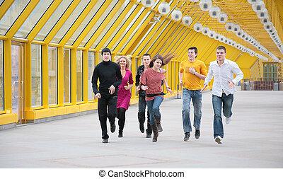 grupo, de, joven, amigos, corre, en, amarillo, puente peatonal