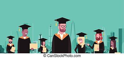 grupo, de, mezcla, carrera, estudiantes, en, tapa graduación, y, bata, asimiento, diploma, encima, moderno, ciudad, edificios, plano de fondo