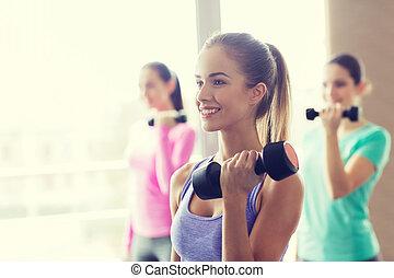 grupo, de, mulheres felizes, com, dumbbells, em, ginásio