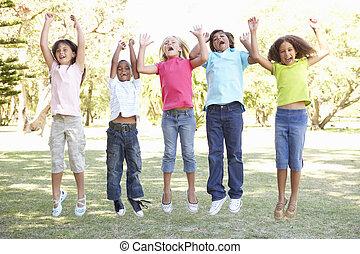 grupo de niños, saltar hacia dentro, aire, en el estacionamiento