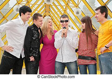 grupo de personas jóvenes, con, micrófono, en, puente peatonal